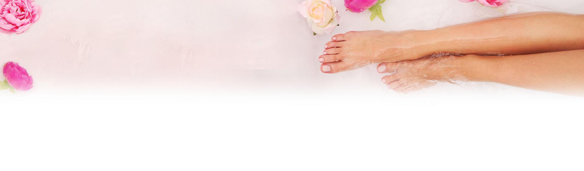 Stopy zanurzone w wodzie na tle róż