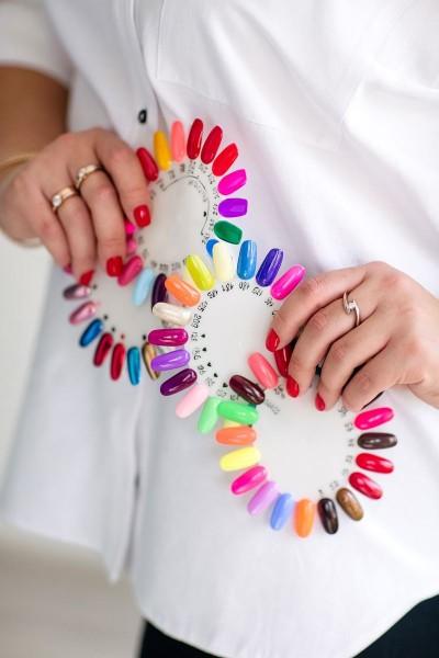 Kobieta z przykładowymi kolorami paznokci w dłoniach