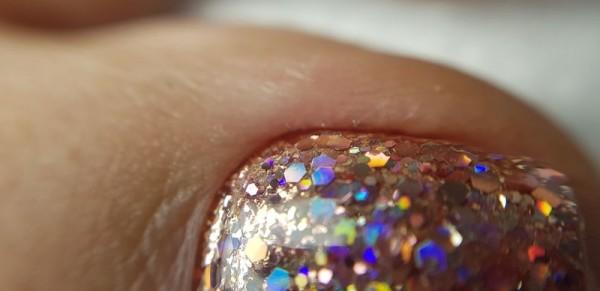 Dłoń z błyszczącym paznokciem we wzorze