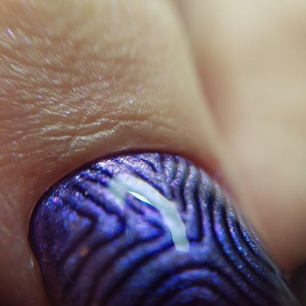 Dłoń z paznokciem w odcieniu niebieskiego z wzorem