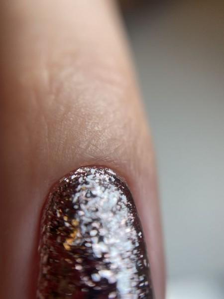 Palec z paznokciem w błyszczącym wzorze