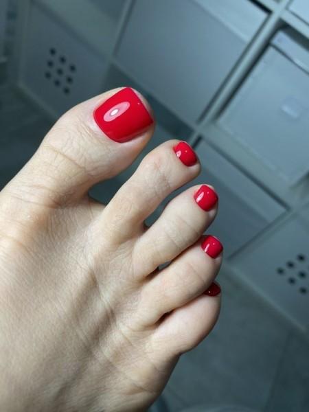 Stopa z paznokciami w odcieniu czerwieni